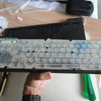 (8) Aqui o teclado, ainda apoiado, já com as borrachas brancas das teclas, a membrana e com a borracha branca de contato que a prende sobre a placa de circuito.