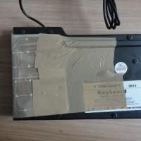 (13) Agora, dobre a membrana e, com a mesma fita adesiva, prenda-a na tampa traseira do teclado.