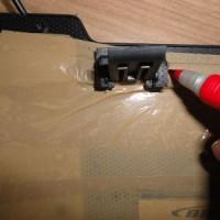 (17) Coloque o pezinho sobre a tampa traseira do teclado, sobre a fita, bem perto do local onde termina a membrana e faça a marcação da posição. O pezinho será colocado nesse ponto.